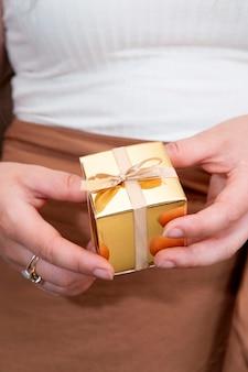 Mãos femininas segurando uma caixa de presente ouro, presente de feriado, aniversário, natal, pai ou mãe, dia dos namorados close-up