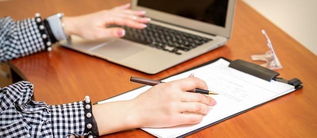 Mãos femininas segurando uma caneta sob o documento e trabalhando com o laptop na mesa em um escritório