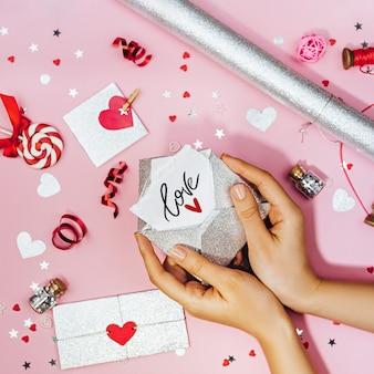 Mãos femininas segurando uma carta de amor em um envelope com a inscrição de amor