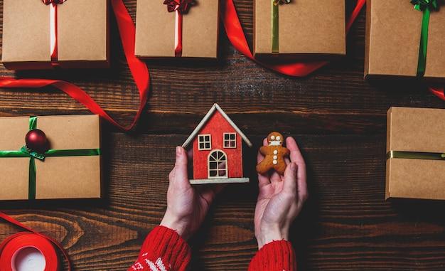 Mãos femininas segurando uma casa de biscoito e brinquedo perto de caixas de presente, sobre a mesa de madeira.