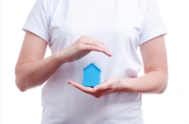 Mãos femininas segurando uma casa em miniatura