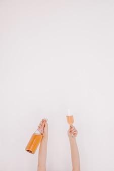 Mãos femininas segurando uma garrafa de champanhe rosa e um copo contra uma parede branca