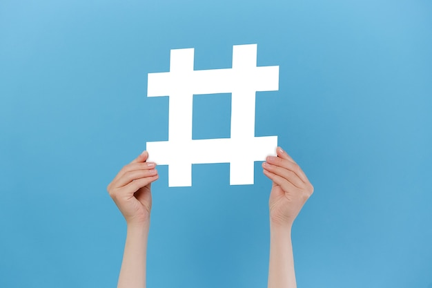 Mãos femininas segurando uma grande placa de hashtag branca