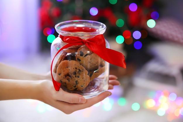 Mãos femininas segurando uma jarra com biscoitos de natal