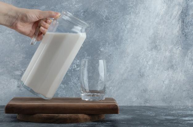 Mãos femininas segurando uma jarra de leite no mármore.