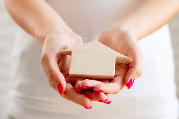 Mãos femininas segurando uma miniatura de casa de brinquedo de madeira close-up