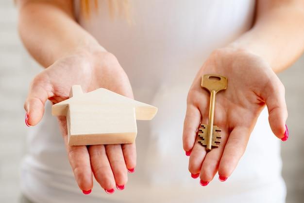 Mãos femininas segurando uma miniatura de casa de brinquedo de madeira