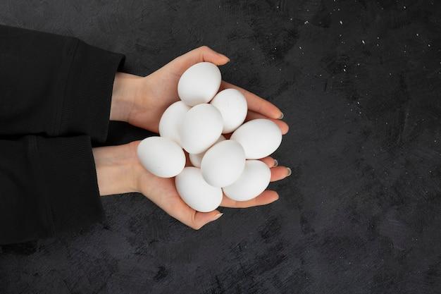 Mãos femininas segurando uma pilha de ovos crus em fundo preto.