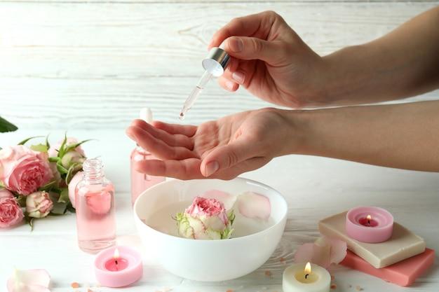 Mãos femininas segurando uma pipeta com óleo essencial de rosa, close-up