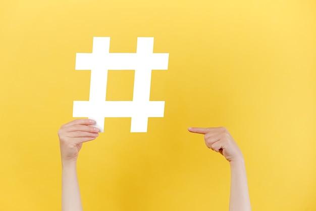 Mãos femininas segurando uma placa de hashtag