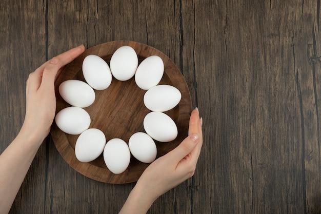 Mãos femininas segurando uma placa de madeira com ovos crus na superfície de madeira.
