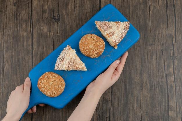 Mãos femininas segurando uma tábua de biscoitos integrais e torta doce na mesa de madeira.