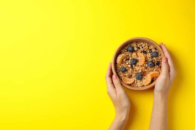 Mãos femininas segurando uma tigela com granola