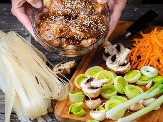 Mãos femininas segurando uma tigela de frango com molho teriyaki e sementes de gergelim