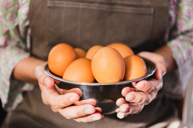Mãos femininas segurando uma tigela de prata com ovos de galinha