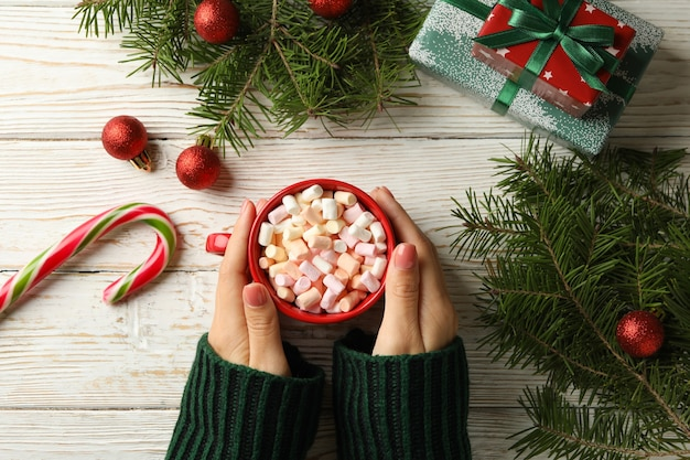 Mãos femininas segurando uma xícara com marshmallow e acessórios de natal