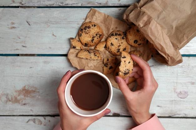 Mãos femininas segurando uma xícara de café e biscoitos na mesa de madeira