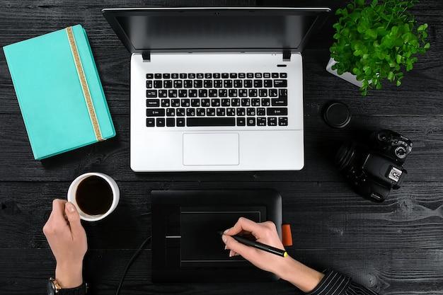 Mãos femininas segurando uma xícara de café e digitando no teclado de um laptop na mesa de madeira preta