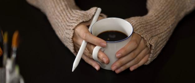 Mãos femininas segurando uma xícara de café e uma caneta stylus enquanto relaxa na sala do escritório
