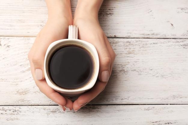 Mãos femininas segurando uma xícara de café na madeira