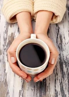 Mãos femininas segurando uma xícara de café na mesa de madeira