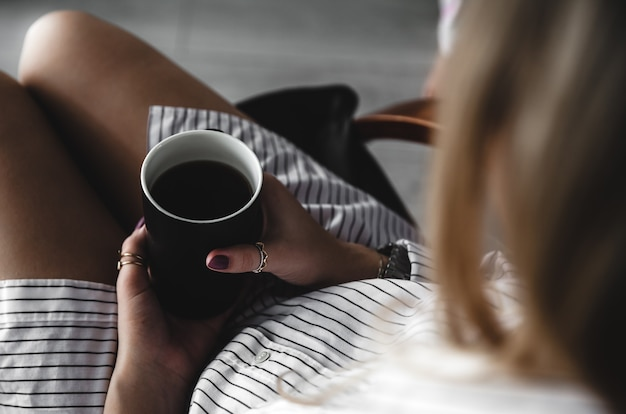 Mãos femininas segurando uma xícara de chá branca, manicure cor de vinho, a garota vestida com uma camisa