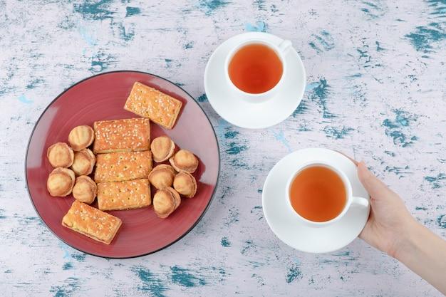 Mãos femininas segurando uma xícara de chá com nozes de shortbread com leite condensado.