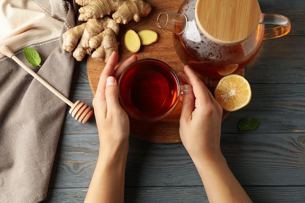 Mãos femininas segurando uma xícara de chá de gengibre