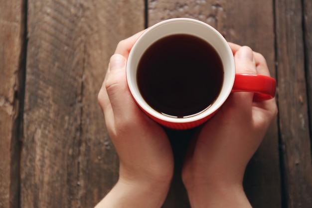 Mãos femininas segurando uma xícara de chá na mesa de madeira