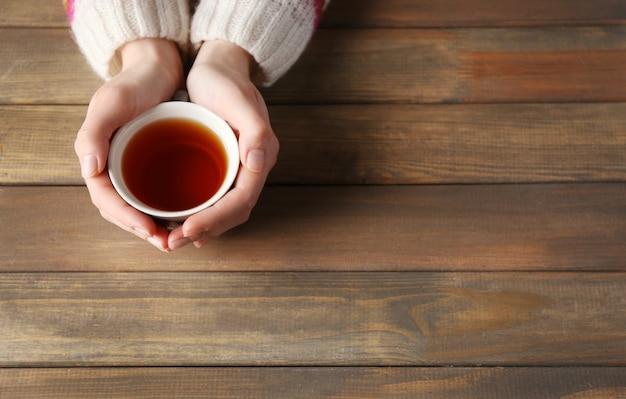 Mãos femininas segurando uma xícara de chá no fundo de madeira