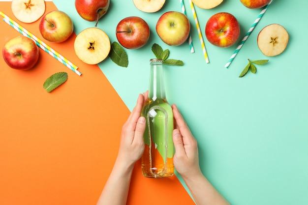 Mãos femininas segurar a garrafa de cidra em dois tons. composição com cidra