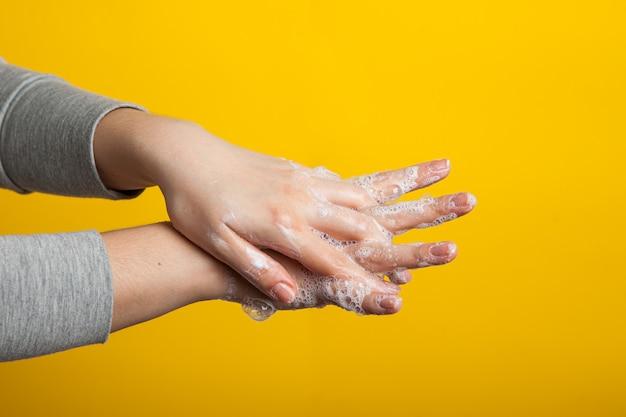 Mãos femininas segurar as mãos de sabão entre os dedos em um estúdio amarelo