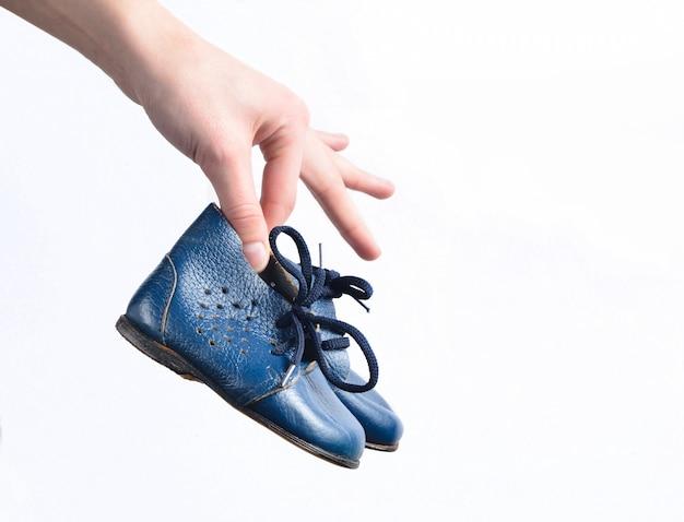 Mãos femininas segurar botas de couro infantil em um branco