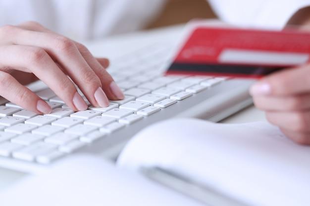 Mãos femininas segurar cartão de crédito, pressionando os botões e fazendo closeup compra on-line.