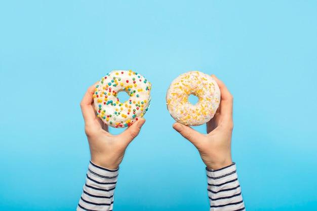 Mãos femininas segurar donuts em um azul. confeitaria conceito, pastelaria, cafetaria