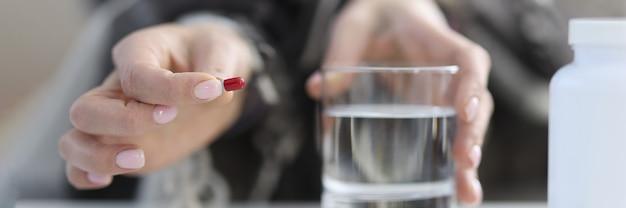 Mãos femininas segurar o comprimido e um copo de água. conceito de tomar medicamentos