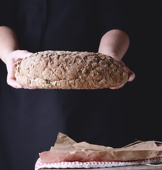 Mãos femininas segurar oval cozido pão de centeio com sementes de abóbora