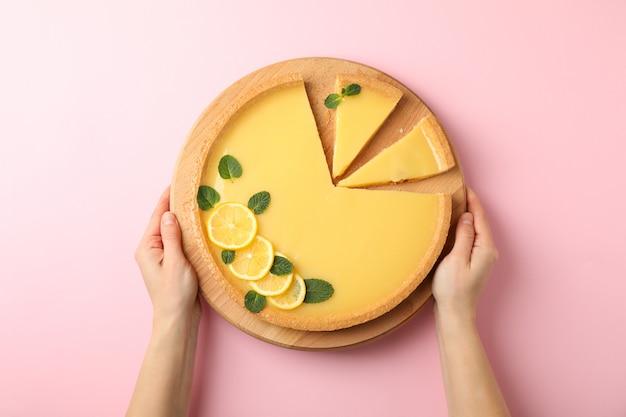 Mãos femininas segurar placa com torta de limão no fundo rosa, vista superior