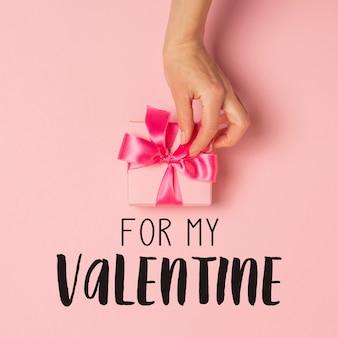 Mãos femininas segurar, receber, receber um presente em uma superfície rosa. dia dos namorados
