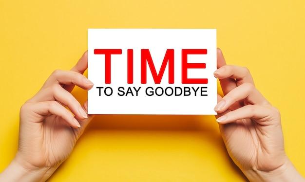 Mãos femininas segurar um cartão com tempo de texto para dizer adeus em uma superfície amarela. negócios, conceito de finanças