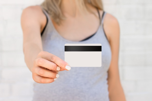 Mãos femininas segurar um cartão de crédito com uma faixa preta contra uma parede de tijolos brancos