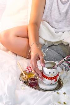 Mãos femininas segurar um copo na forma de um boneco de neve com doces de natal
