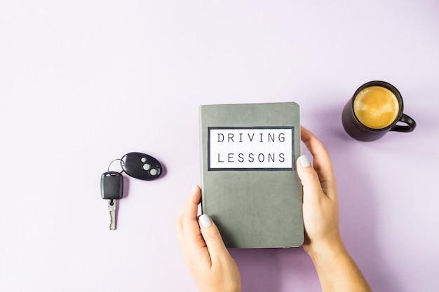 Mãos femininas segurar um livro de treinamento para aulas de condução e estudar as regras de trânsito