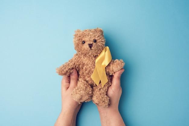 Mãos femininas segurar um pequeno urso de pelúcia com uma fita amarela dobrada em um loop em uma superfície azul