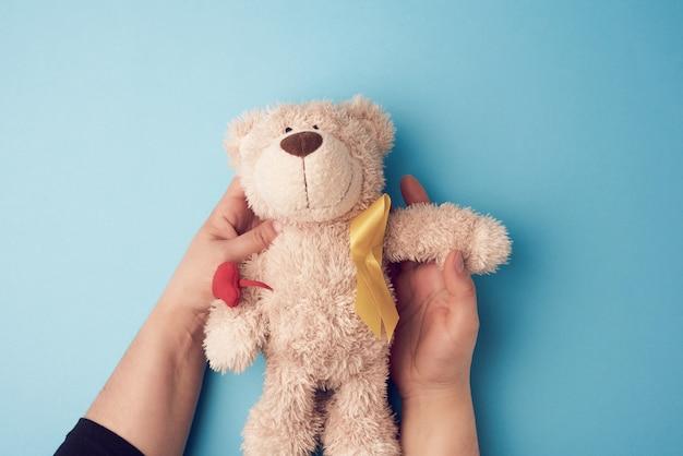 Mãos femininas segurar um pequeno urso de pelúcia com uma fita amarela dobrada em um loop