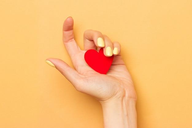 Mãos femininas segurar um símbolo do coração de madeira.