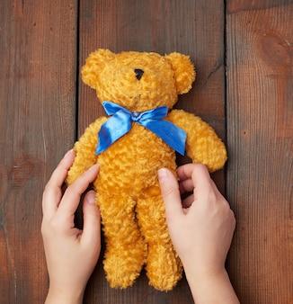 Mãos femininas segurar um ursinho de pelúcia brinquedo em uma mesa de madeira marrom