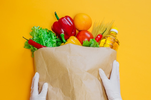 Mãos femininas segurar um vermelho, pimenta amarela, pimentão, óleo de girassol, tomate, laranja, macarrão, alface no pacote de papel artesanal, um conjunto de comida vegetariana em um espaço laranja