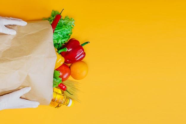 Mãos femininas segurar um vermelho, pimenta amarela, pimentão, óleo de girassol, tomate, laranja, macarrão, alface no pacote de papel artesanal