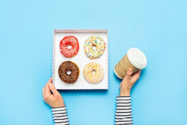 Mãos femininas segurar uma caixa com donuts, uma xícara de café em um azul. loja de confeitaria conceito, bolos, café.